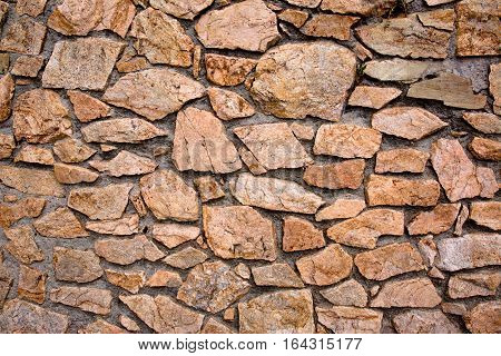 Abstract Grunge Stonewall Background. Decorative Finishing Wall Fence of natural stone. Rough Surface Rock Texture Horizontal Image Close up