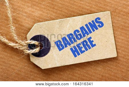 Paper luggage or price tag with the text Bargains Here with string on brown wrapping paper