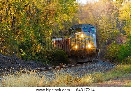 Railroad freight train rounding a curve in the tracks in the country side. All trademarks have been removed for use.