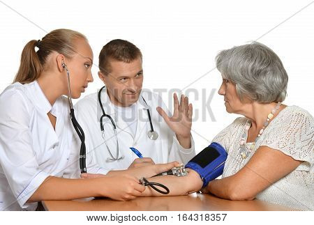 man and woman doctors with patient measuring preasure