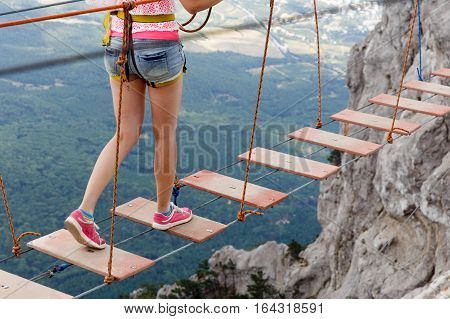 Young woman walking on rope ladder in mountains above forest