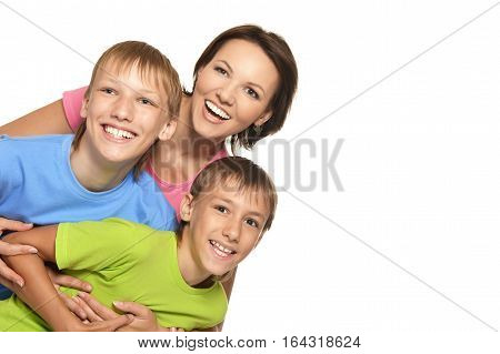 mother posing with her sons, against white