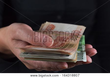 Woman's hand giving away money, close up