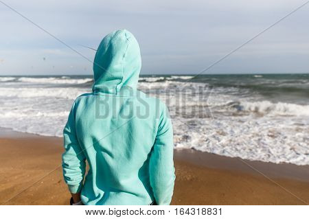 Girl in jacket with hood is back at seaside
