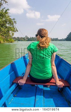 Attractive brunette enjoying boat ride in sunny weather. Lake Phewa, Pokhara in Nepal.