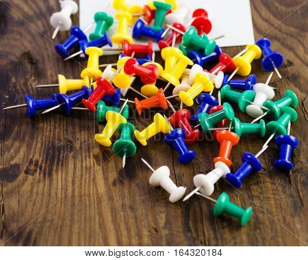 Various Color Thumbtacks And Note On Distressed Wood