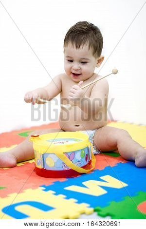 Baby kid playing musical toy. the boy learns play the drum