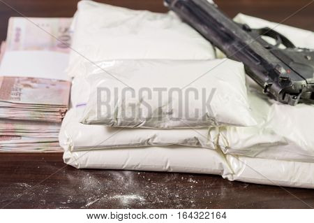 Bags Of Drugs, Pistol And Money On Table