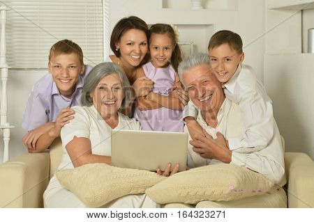 big family posing in home interior, mother, grandparents and kids