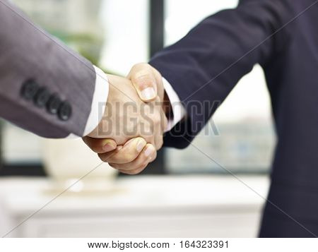close-up low angle view of a firm handshake in office by two asian businessmen.