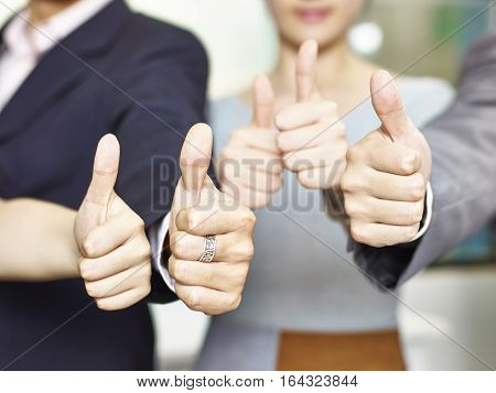 small group of asian business people showing the thumb-up hand signs.