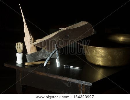 Vintage barber or shaver tools on wooden table. Old razors with blades copper basin shaving brush broken axe and towel on dark background