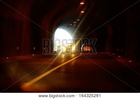 Moving cars with included headlights inside tunnel with soft iluminated exiting to white calm light.