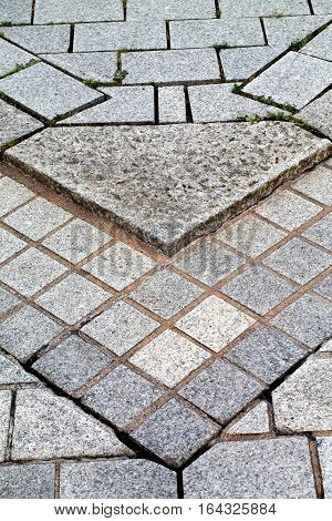 Gray cement bricks  and little stones building a floor. Street pavement.