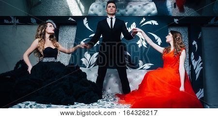 young handsome man in black suit and bow with pretty sexy women in red elegant evening dress with skirt and long curly hair on bed in bedroom