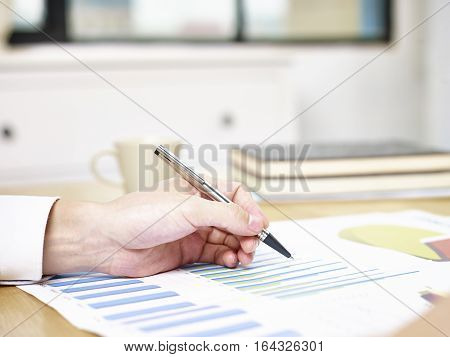 close-up of a hand holding a pen pointing at business reports on desk in office.