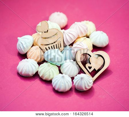 meringues in pastel colors with wooden figures of heart and cupcake on magenta background