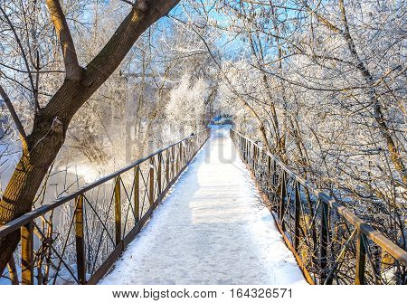 Bridge over the river and trees covered with hoarfrost bright sunny day in winter