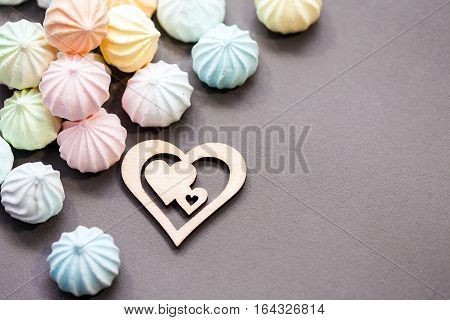 meringues in pastel colors with wooden figure of heart on grey background. St Valentines's Day