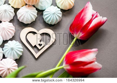 meringues in pastel colors with wooden figure of heart and three red tulips on grey background. St Valentines's Day