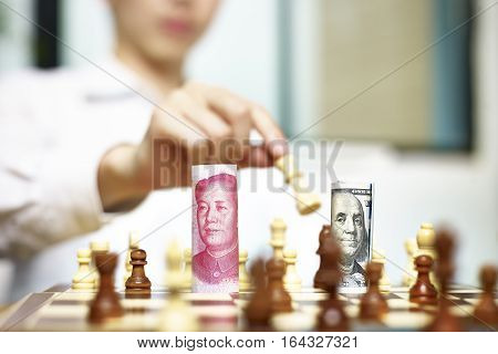 U.S. Dollar (USD) and Chinese Yuan (CNY or RMB) bills on a chess board concept for currency games.