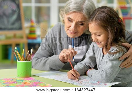 Potrait of grandmother with her granddaughter drawing together