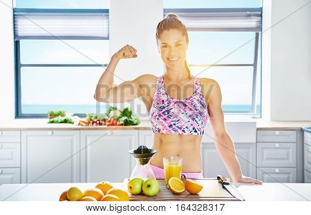 Young Muscular Woman Smiling And Showing Bicep