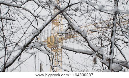 Yellow construction crane in snow winter, telephoto
