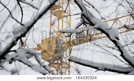 Yellow construction crane in snow winter, close up, telephoto