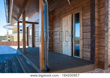 The porch of a new wooden house. Suburban house detail.