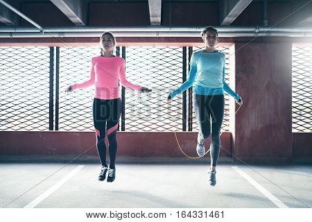 Young pretty athletics girls skipping on drill at gym against barred window.