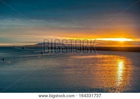 Sun sets behind Santa Cruz Island as boats return into Ventura Harbor.