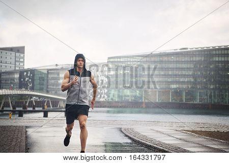Sportive Male Running Down Street In Rain