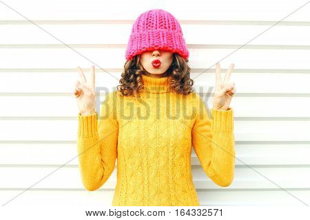 Fashion Happy Woman Blowing Red Lips Makes Air Kiss Wearing Colorful Knitted Pink Hat, Yellow Sweate