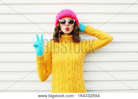 Fashion Woman Blowing Red Lips Wearing Colorful Knitted Yellow Sweater Pink Hat In Gloves Over White
