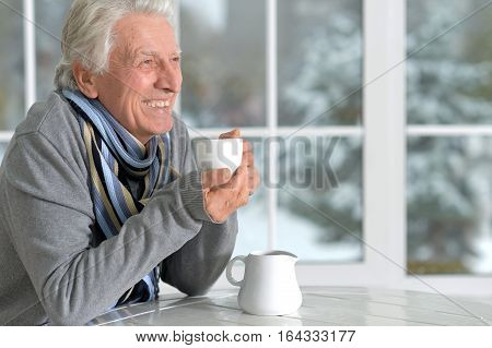 mature man drinking coffee, in cafe near window