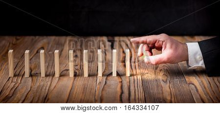 Chain Reaction Domino Effect In Business Concept Businessman Just Starting Dominoes Continuous Toppling On Rustic Wooden Desk