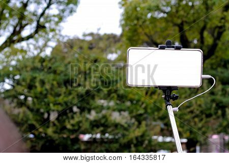 Mobile phones and selfie stick with green tree on background