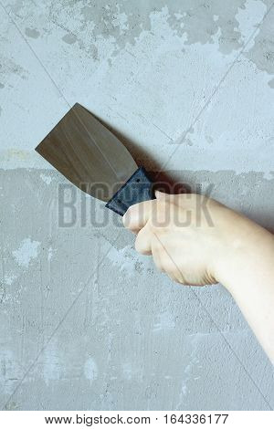 Female hand with a spatula concrete wall plasters in room during repair vertical photo