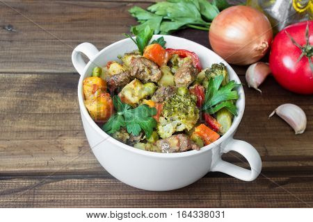 beef meat stewed with potatoes, carrots and spices in ceramic pot on wooden with ingredients background