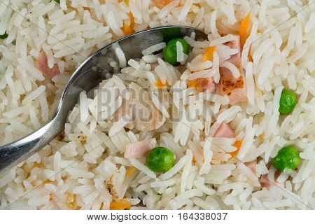 Meal background. Oriental rice dish with mixed meat boiled egg fresh vegetables like peas and carrot. Spoon and traditional Thai Food.