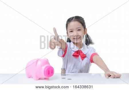 Isolated asian little girl in Thai student uniform showing thumb up with piggy bank and stack of coins selective focus on face shallow depth of field