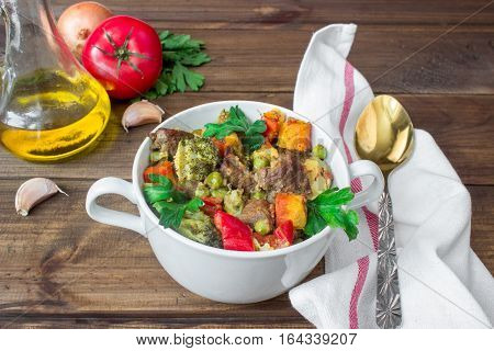 served beef meat stewed with potatoes, carrots and spices in ceramic pot with ingredients on wooden background