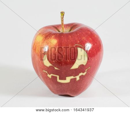 1 red apple with a grim face on a white background