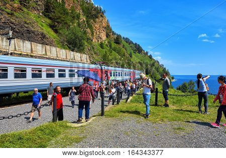 KIRKIREY IRKUTSK REGION RUSSIA - July 292016: Baikal Express. Tourists from different countries visiting sights of Circum-Baikal Railway. Stopping 123 kilometer - a place of joining Trans-Siberian Railway in 1904