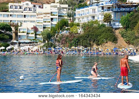 BALI, CRETE - SEPTEMBER 16, 2016 - Holidaymakers on paddle boards with tourists relaxing on the beach to the rear Bali Crete Greece Europe, September 16, 2016.