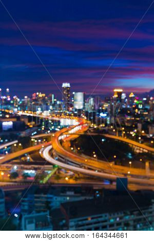 Blurred lights highway interchanged with city downtown with beautiful after sunset sky background