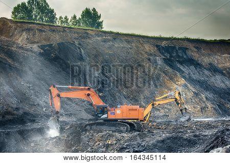 NOVOKUZNETSK, RUSSIA - JULY 26, 2016 Big orange and yellow excavators at worksite