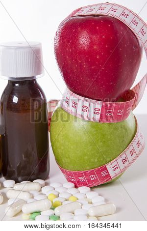 tablets and drugs for weight loss. two apples with measuring tape. Focus 60 and 90 cm
