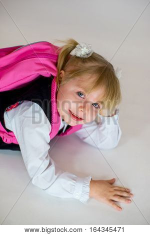 Portrait Of Young Lying Schoolgirl With Schoolbag